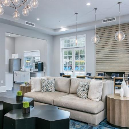 Alvista Metrowest Orlando Florida clubhouse lounge with upholstered seating, dining style table and chairs and adjacent commercial kitchen with access to pool deck