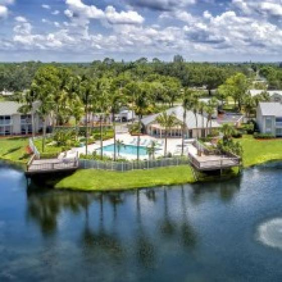 Alvista Golden Gate aerial photo of community lake, pool deck, clubhouse and residential buildings with lush tropical landscaping and clouds in the sky
