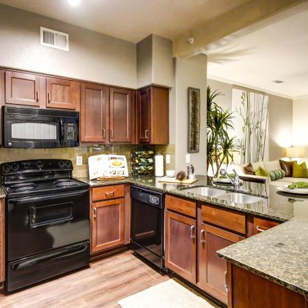 Beautiful kitchen featuring an island, stainless steel appliances, tile back splash and granite counter tops.