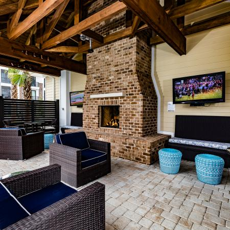 Outdoor pool cabana with community seating, fireplace and HDTVs