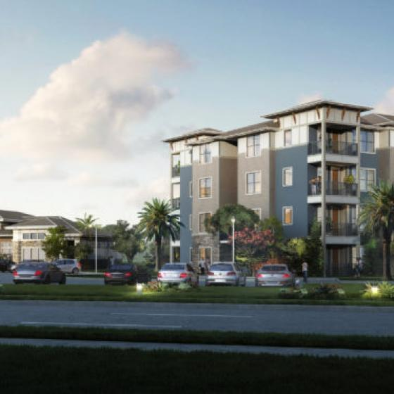 Tomoka Pointe building exterior with four-stories, next to a clubhouse with parking and two people looking at the exteriors
