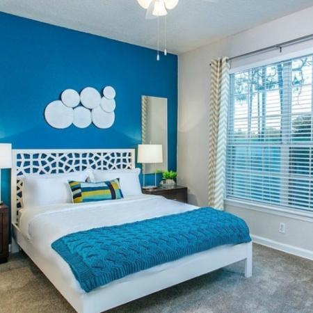 Alvista Metrowest Orlando Florida furnished bedroom with double window with blinds, carpeted flooring, ceiling fan with light
