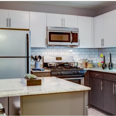 Model kitchen with stainless steel appliances, granite countertops, an island and subway tile backsplash