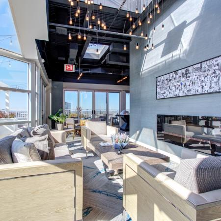 Rooftop entertainment lounge with floor-to-ceiling windows and a fireplace