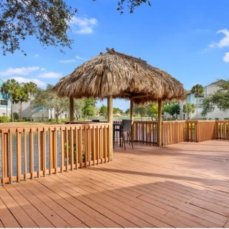 Side picture of the outside tiki bar that sits within the large red wood deck overlooking the community lake.