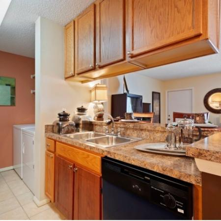 Kitchen with faux granite, light maple cabinetry , washer /dryer and large bar area.