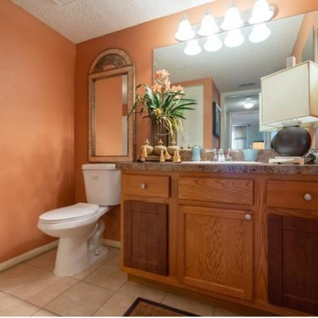 Bathroom withlLight maple wood cabinetry, tile flooring with tulip style vanity lighting.