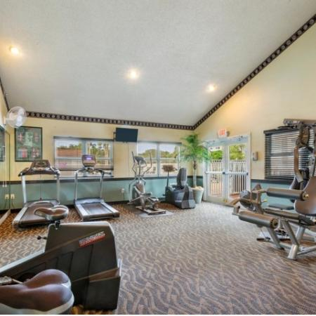Carpeted fitness center with large windows and wall television for viewing .