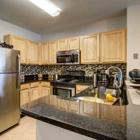U-shaped kitchen with black countertops, stainless steel refrigerator, microwave and stove. Ample cabinet space with blonde cabinets above and below counter with multi-colored tile backsplash
