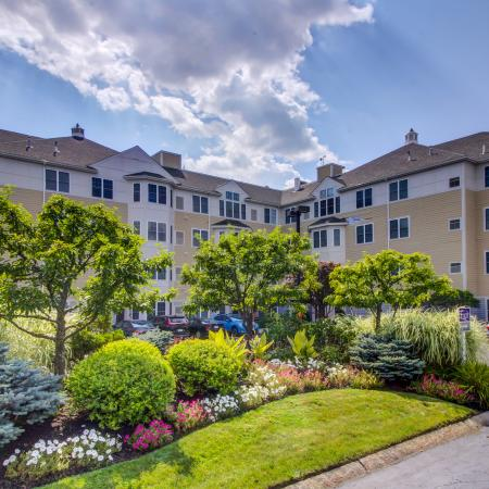 View of community with lush and colorful landscaping with apartment building parking lot of cars