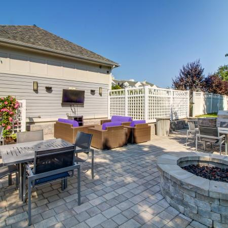 Fire pit with four person tables and grilling station with gas grill. Mounted outdoor TV with additional soft seating positioned in front.