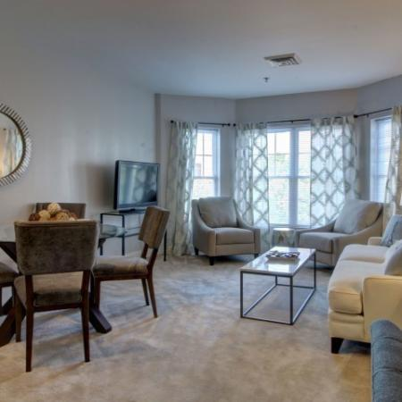Carpeted living room and dining room. Four person table with chairs in foreground with couch to the right. Coffee table is placed in front of couch facing TV on opposite wall. Two chairs in front of bay windows in the background and to the