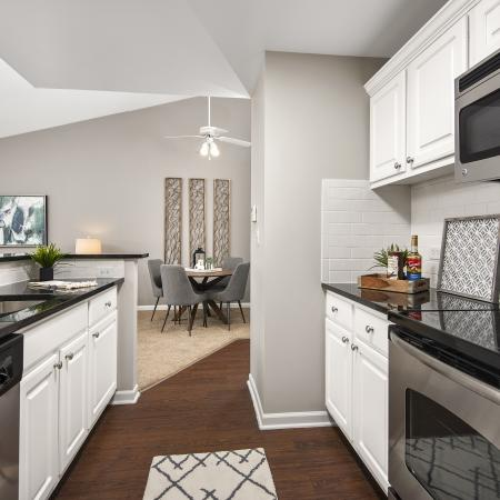 Model kitchen with granite countertops, ceramic tile backsplash and stainless steel appliances