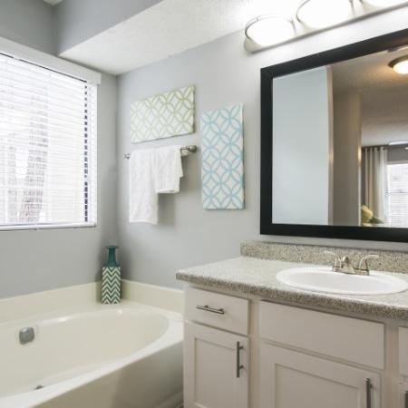 Bathroom with white shaker style cabinets, garden tub and framed mirror