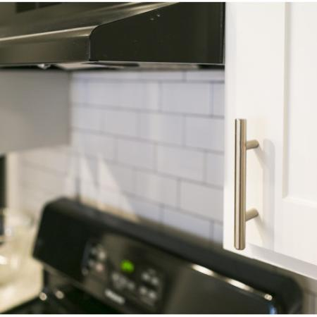 White shaker style kitchen cabinet with stainless pulls and subway tile backsplash