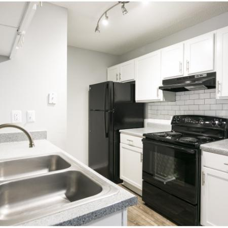 White shaker style kitchen cabinet with stainless pulls and subway tile backsplash with black appliances