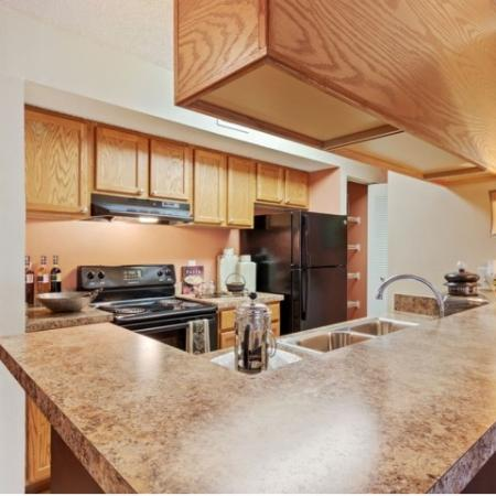 Kitchen with faux granite, light maple cabinetry and large bar area.