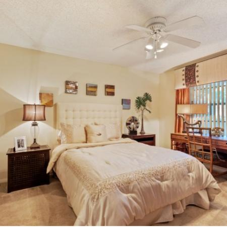 Large master bedroom with white ceiling fan and vertical slat blinds.