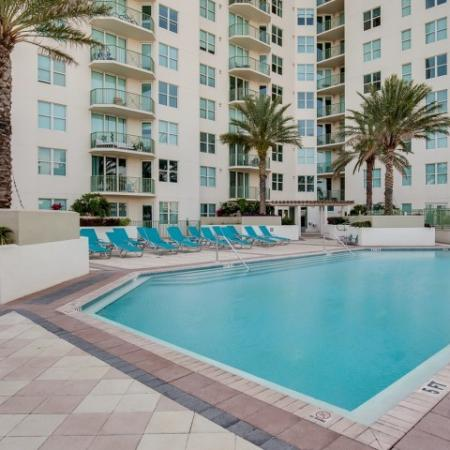 The Strand Jacksonville pool deck flanked by magnificent palm trees and a high-rise building with patios