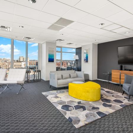 Furnished media and party room featuring a flat-screen TV and floor-to-ceiling windows with a city view