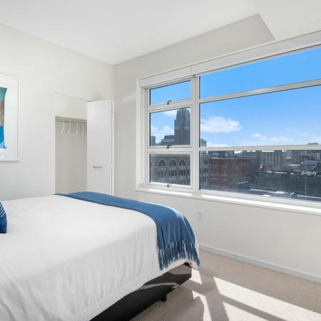 Furnished model bedroom with a closet and city views