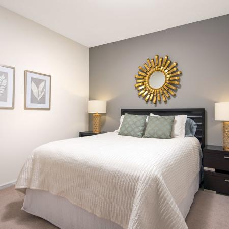 Furnished model bedroom with a queen sized bed, end tables, and lamps