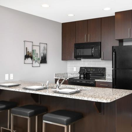 Furnished model kitchen with espresso cabinetry, black appliances, a tiled backsplash and a matching island