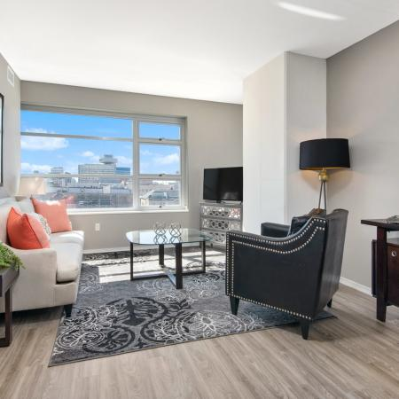 Furnished living room with a flat screen TV, vinyl plank flooring and city views