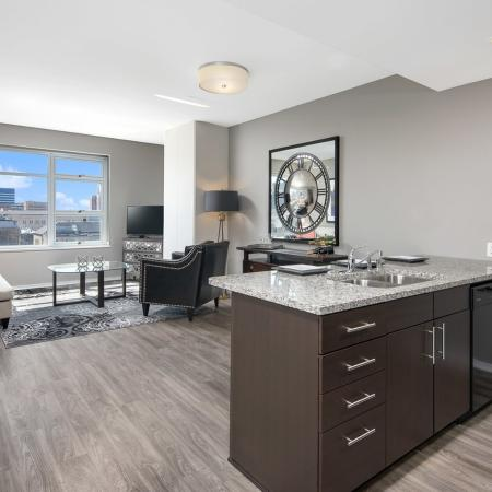 Furnished model living room with a city view and kitchen island
