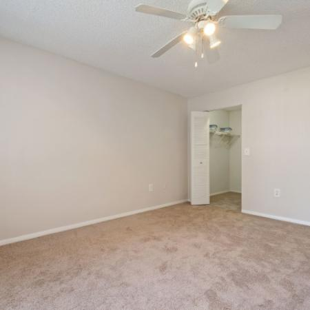 Spacious master bedroom with beigh plush carpet and large open closet.