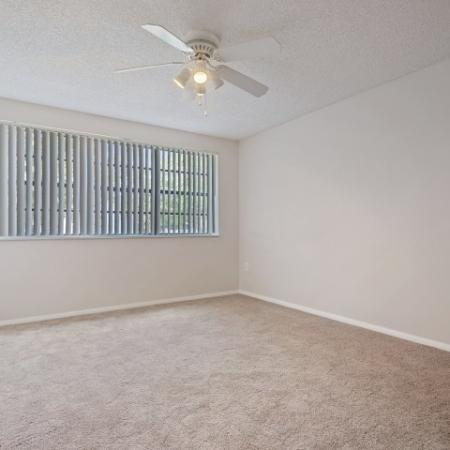Large 2nd bedroom with vertical blinds, plush beigh carpet and white ceiling fan.