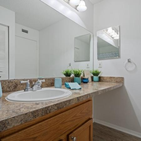 Master bathroom with vanity style cabinetry , a shower tub comination , linine closet and wood like flooring.