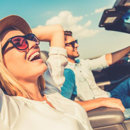 Young happy couple riding in convertible on sunny day with the top down