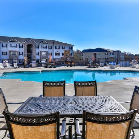 Sparkling pool with lounge chairs, outdoor tables with chairs and views of several apartment buildings