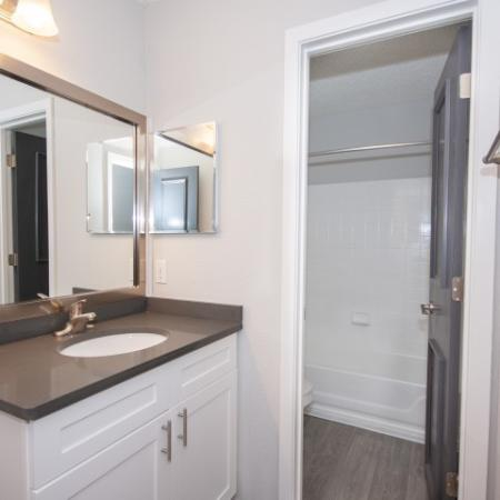 Water closet in the bathroom with framed mirror