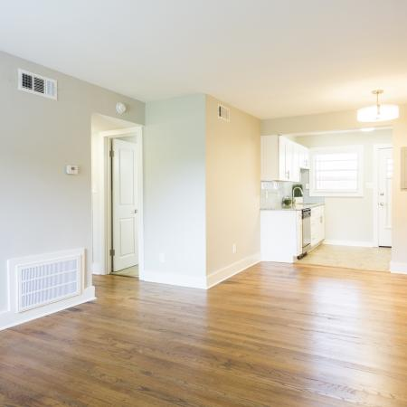 Remodeled vintage living room with plank flooring looking into the kitchen