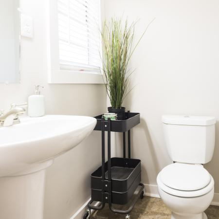 Updated, light and airy bathroom with a pedestal sink and shower/tub combo