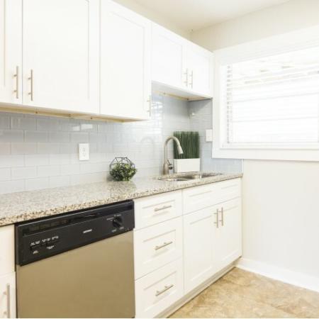 Modern kitchen with white cabinets, subway tile backsplash, and granite countertops