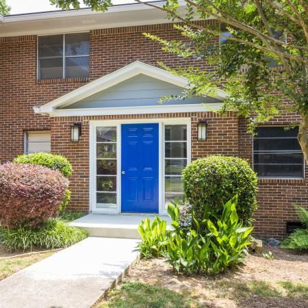 Exterior entryways with blue doors surrounded by trees