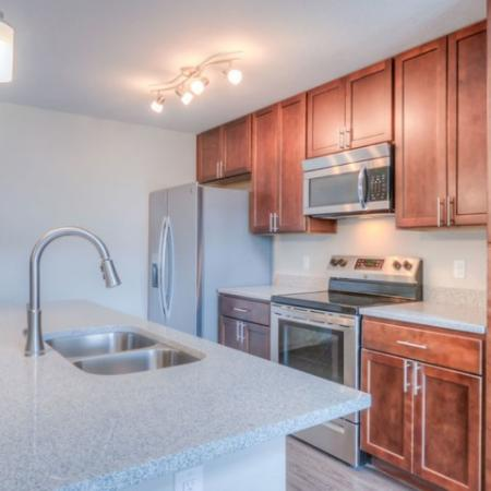 San Mateo Apartments Kissimmee Florida kitchen with stainless steel appliances, wood cabinets, island kitchen with double sink and gooseneck faucet
