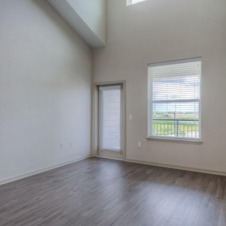 San Mateo Apartments Kissimmee Florida living room with tall ceilings and French door leading to patio with wood plank flooring