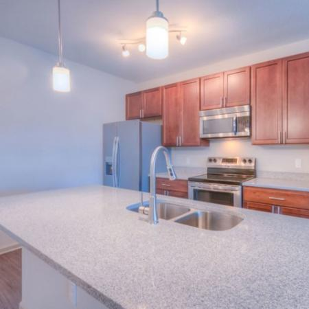 San Mateo Apartments Kissimmee  Florida island kitchen with wood cabinets, stainless steel appliances and granite countertops
