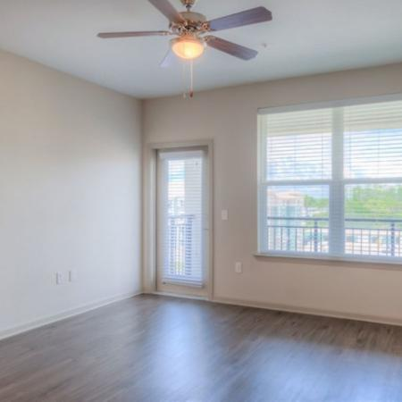 San Mateo Apartments Kissimmee Florida living room with plank flooring, ceiling fan, French door to patio