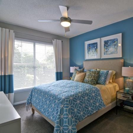 Large bedroom with carpet and a ceiling fan