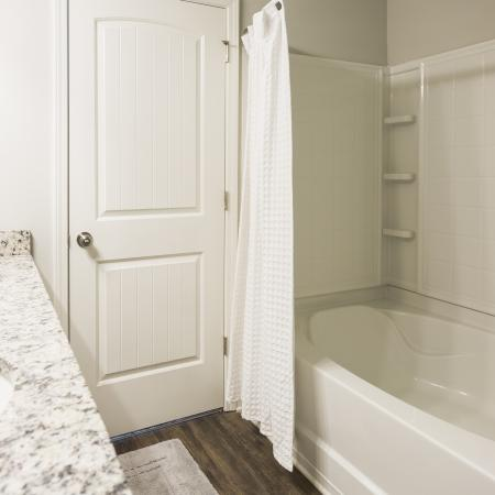 Shower Garden tub combo with faux wood flooring in the bathroom
