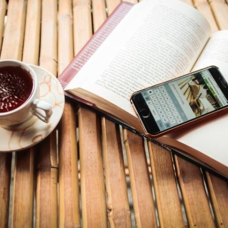 Coffee cup, phone, and open book on table