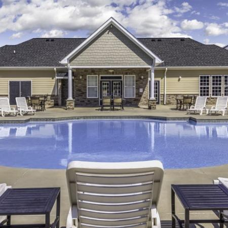 Sparkling pool with lounge chairs and back view of clubhouse