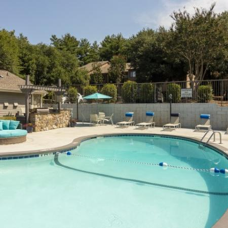 View of the swimming pool with surrounding lounge chairs, outdoor gas grilling station and soft seating