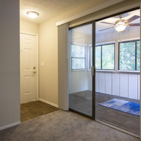 View of front entry into apartment home and sunroom with hardwood inspired flooring