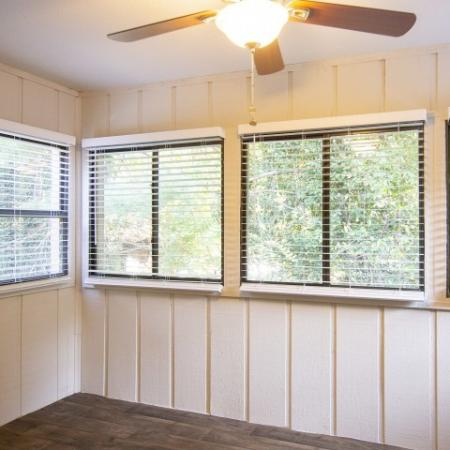 Enclosed sun porch with multiple windows, wood inspired plank flooring and ceiling fan with light fixture